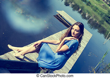 portrait image of romantic young brunette pretty lady having fun relaxing sitting in casual blue dress on river or lake pier dreaming on summer sunny day outdoors copy space background