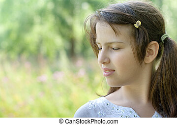 Portrait in profile of cute brunette girl standing outdoor relaxing with closed eyes