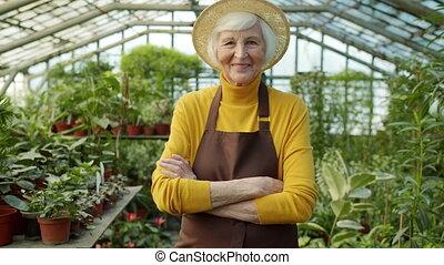 portrait, jardinier, sourire, serre chaude, appareil photo, cligner, debout, femme regarde, traversé, personne agee, bras