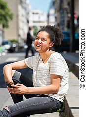 laughing young african american girl sitting outside in city holding mobile phone