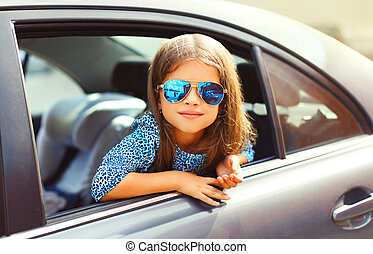 Portrait little girl child sitting in car, passenger looks out of car window