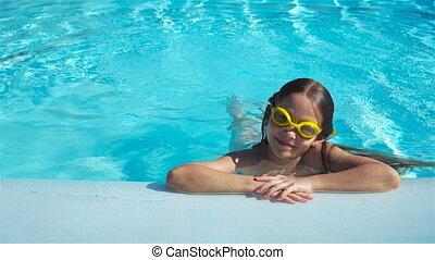 Portrait little girl having fun in outdoor swimming pool. Kid enjoying vacation