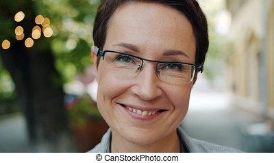 portrait, lunettes, femme affaires, appareil photo, mûrir, sourire, gros plan, dehors