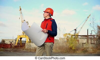portrait man builder in orange helmet looks instruments project against blue sky and building