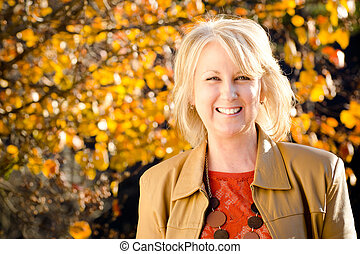 Fall portrait of happy middle-aged blonde woman