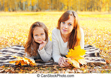 Portrait mother and child together with yellow maple leafs lying on the plaid in sunny autumn day