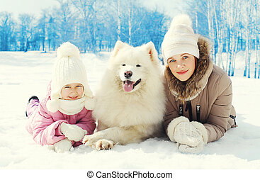 Portrait mother and child with white Samoyed dog together lying on snow in winter day