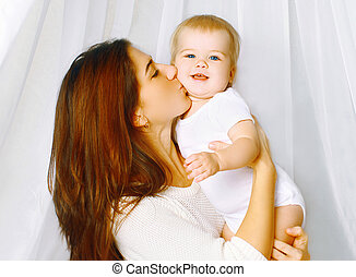 Portrait mother kissing baby on the bed home