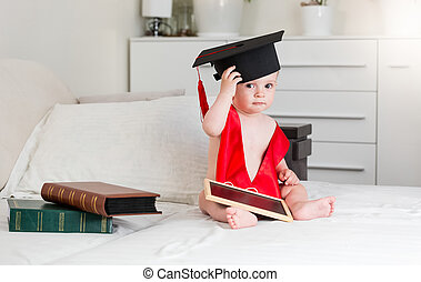Portrait of 10 months old baby boy with books wearing...