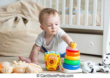 Portrait of 10 months old baby playing with colorful toy tower