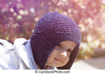 Autumn portrait of 2-3 years old child in garden. Fall season. Close-up view of cheerful sweet mixed-race baby boy in knitted cap