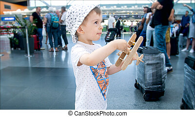 Portrait of 2 years old toddler boy playing with toy airplane in airport