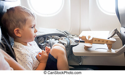 Portrait of 2 years old todler boy with toy wooden airplane during long flight