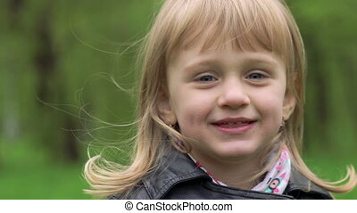 Portrait of 3 years old girl smiling on a camera. Slowly