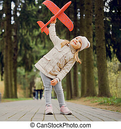 portrait of 3 years old girl with a toy airplane in her hands in the park