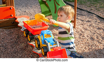 Portrait of 3 years old little boy playing in sandbox with toy truck and trailer