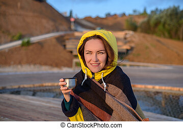 Portrait of 30 years old woman in yellow jacket and plaid with thermos mug in hand smiling looking at sunrise