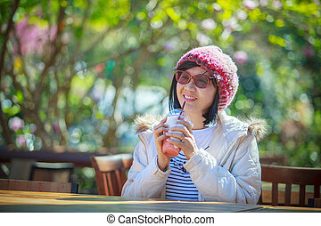 portrait of 40s years asian woman with cool juicy drinking bottle in hand with happiness emotion sitting in beautiful park background