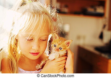 Portrait of 6 years old girl with cute red kitten