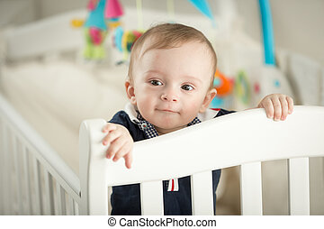 Portrait of 9 month old boy standing in white cradle