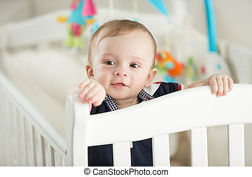 9 month old boy teething and posing in white cradle