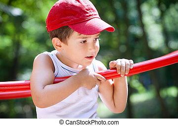 3-4 years old boy standing on a playground in a red cap on the blurred natural background