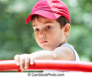 Portrait of a 3-4 years boy playing on the playground....
