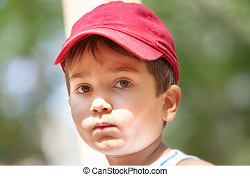 Portrait of a 3-4 years boy in a red cap on the blurred...