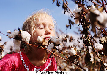 Portrait of a adorable little girl outdoors in the cotton field