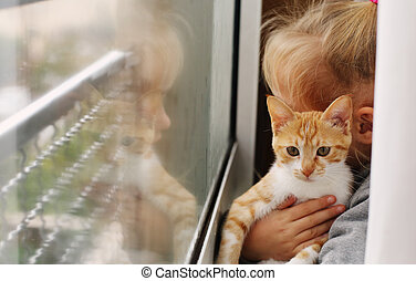 Portrait of a adorable little girl with red kitten