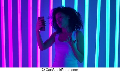 Portrait of a young cute african american woman emotionally talking through a video call on her smartphone. The girl waves her hand, welcoming the interlocutor, to the question of how things are, she answers so so, accompanying the answer with gestures. The girl poses in the studio against the ...