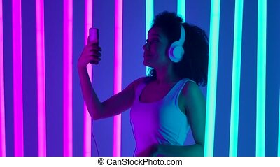 Portrait of a young cute African American woman in big white headphones connected to a smartphone talking on a video call. The girl waves her hand, welcoming the interlocutor, to the question, how are you, she answers so so, accompanying the answer with gestures. The girl poses in the studio against...