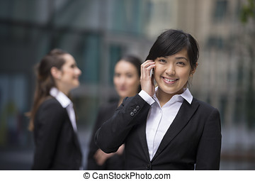 Asian businesswoman standing outside using mobile phone.