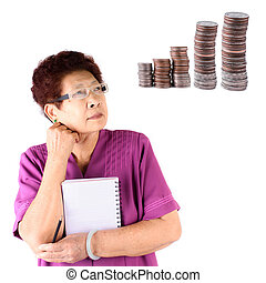 Portrait of a Asian serious senior woman holding notebook and pencil, looking at coins stack