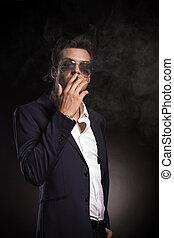 attractive young business man smoking o cigarett