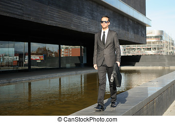 Portrait of a attractive young business man walking in the...