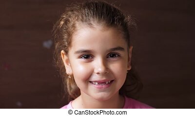 Portrait of a baby girl with a toothless smile. The child ...