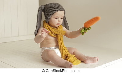 Portrait of a baby in a bunny suit. Little boy laughs and plays with toy