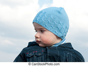 Portrait of a baby in blue at the spring sky