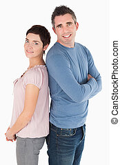 Portrait of a back to back couple against a white background