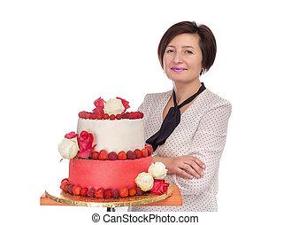 Portrait of a baker girl near a wedding cake.
