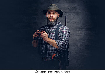 Portrait of a bearded hunter in a fleece shirt and hat holds binoculars while standing with a rifle behind his back.