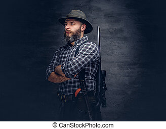 Portrait of a bearded hunter in a fleece shirt and hat standing with a rifle behind his back.