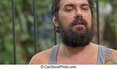 Portrait of a bearded man talking while drinking a beer -...