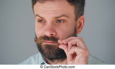 Portrait of a handsome bearded man twists his mustache
