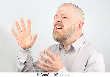 Portrait of a bearded man with raised hands with emotions on a light background