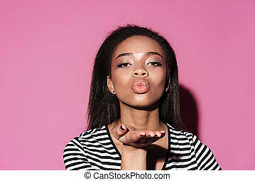 Portrait of a beautiful african woman blowing kiss to camera