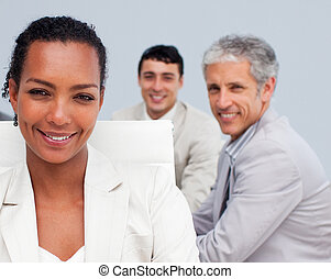 Portrait of a beautiful Afro-American businesswoman smiling in a meeting with her colleagues working in the background