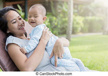 beautiful asian mother having fun with his baby