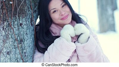 Portrait of a beautiful Asian woman against the background of the snow park.